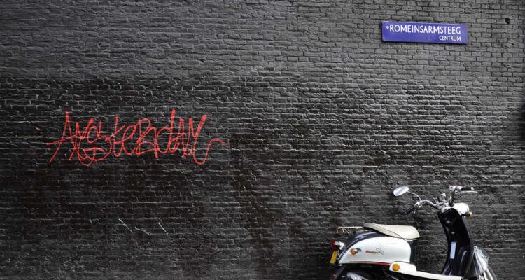 vespa appoggiata su un muro ad Amsterdam