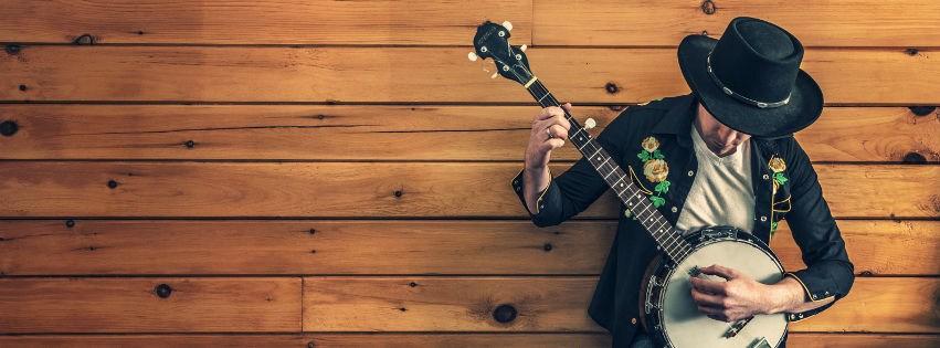 profilo facebook immagine copertina con suonatore di banjo appoggiato ad una parete di legno