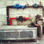 Un clochard seduto su un impianto a stazione termini