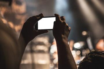 Mani che tengono un cellulare, durante un evento