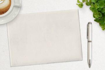 Tavolo con blocco, penna, cappuccino e pianta