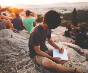 Un ragazzo scrive su una montagna circondato da altre persone