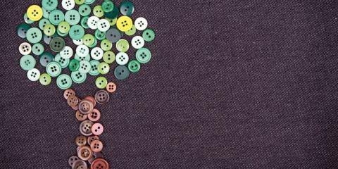 Albero fatto di bottoni cucito su una stoffa denim
