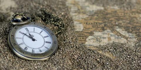 Un orologio da taschino sulla sabbia e una cartina antica