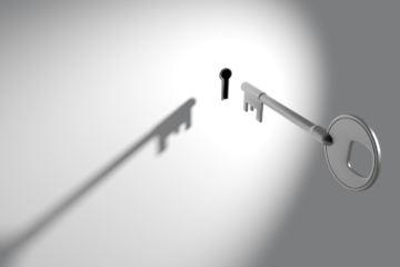 Una chiave che si sta inserendo in una parete bianca