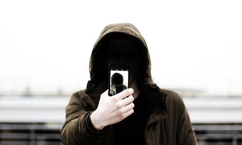 Ragazzo incappucciato e con il volto in ombra, fotografa se stesso
